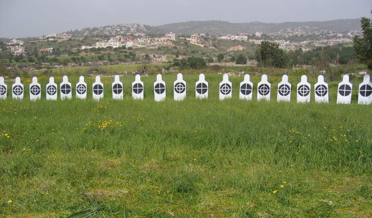 White human figures in line with black targets on their chest