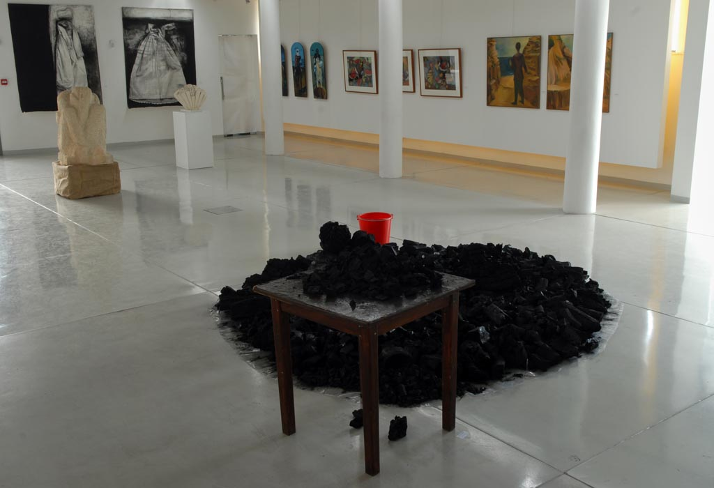 A mount of charcoal, a table and a red bucket
